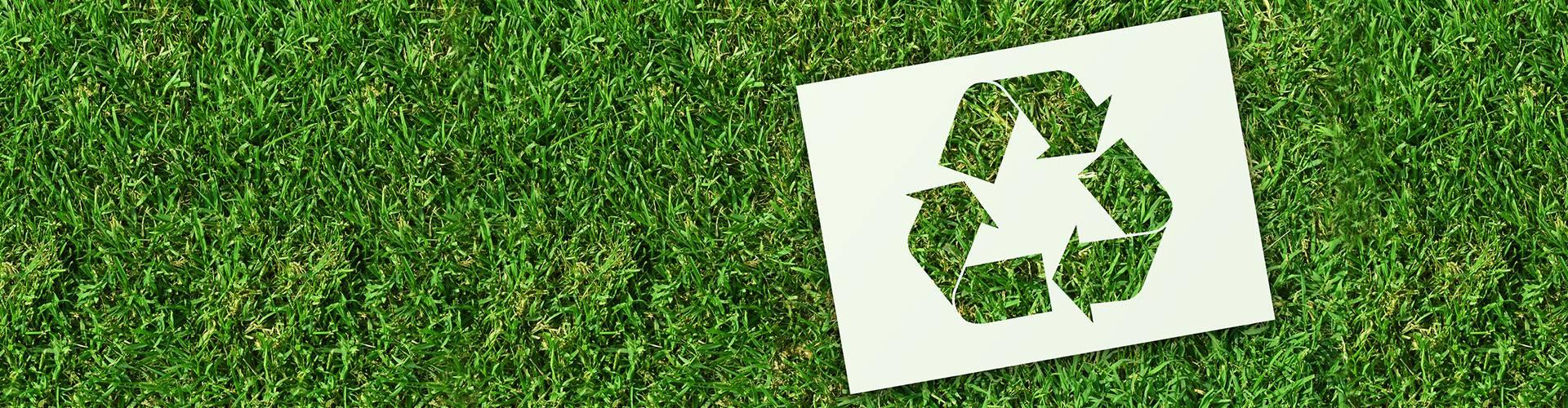 Znaczek recyklingu na trawie